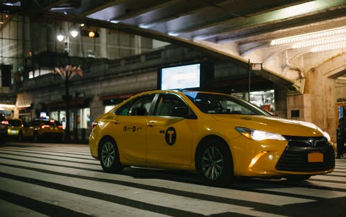 Expensive yellow taxi car riding on New York City street under illuminated bridge at night