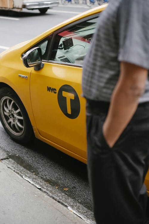 Man with hands in pocket waiting near yellow taxi