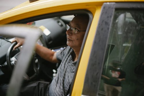 黃色汽車方向盤的中年駕駛員