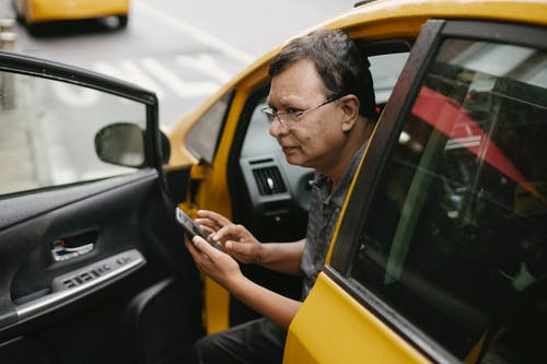 Crop Asian man sitting in parked yellow taxi car with open door and using smartphone while looking away