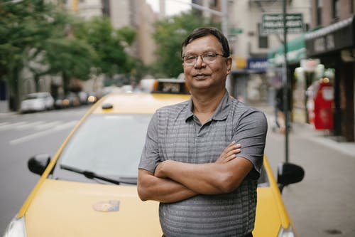 Content ethnic man standing near car