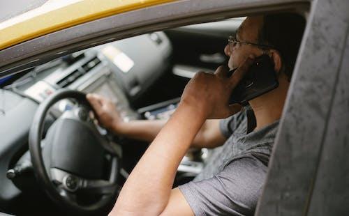 重點突出的駕駛員在汽車上的智能手機上講話