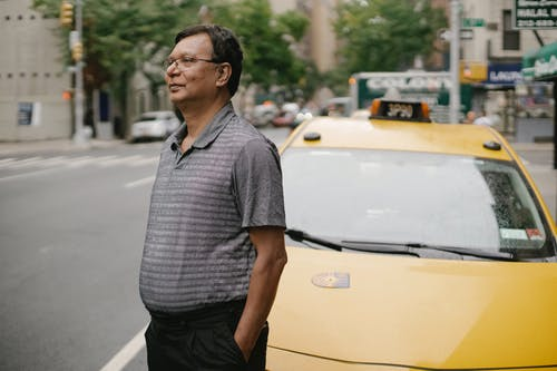Side view of calm ethnic middle aged male in eyeglasses standing with hand in pocket on road near yellow taxi on street with blurred background