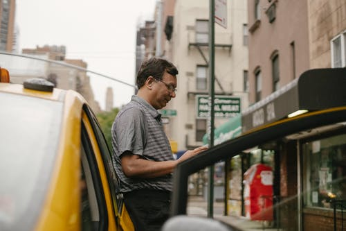 Thoughtful ethnic man leaning on car