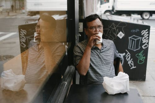 Thoughtful ethnic man drinking coffee in street cafe