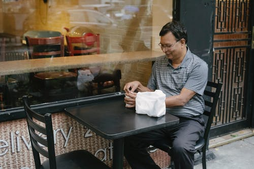 Content ethnic man in street cafe with cup