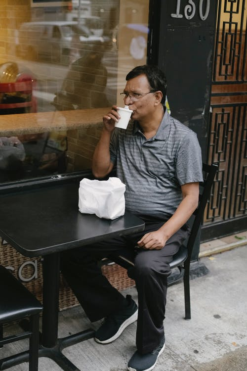 Ethnic man sipping coffee in street
