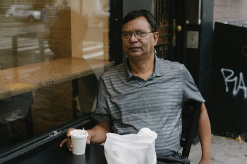 Serious ethnic man with coffee on terrace