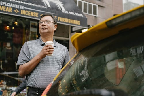 Serious ethnic man with coffee near car