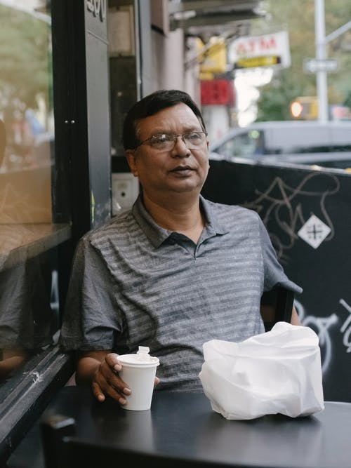 Thoughtful ethnic man at table with bag and coffee