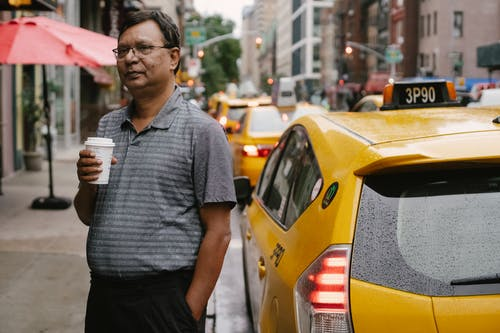 Ethnic man with beverage near taxi