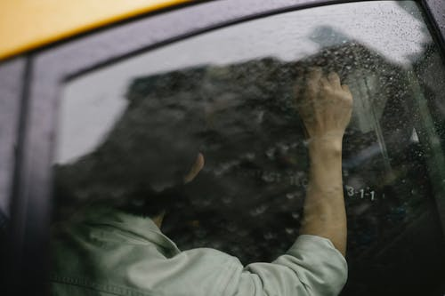 Unrecognizable man sitting on backseat of yellow cab on rainy day
