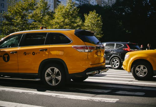 Yellow taxi cars and black SUV driving along road with pedestrian crossing in city centre on summer sunny day