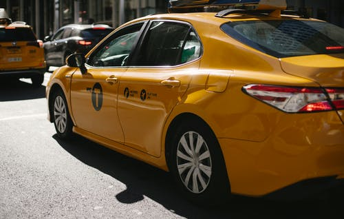 Shiny yellow taxi driving along busy street in downtown