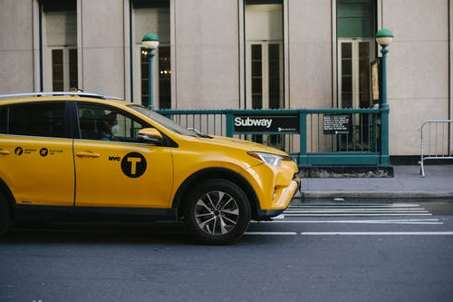 Contemporary yellow taxi with driver in medical mask standing on empty road near modern building and subway station entrance during coronavirus pandemic in New York USA