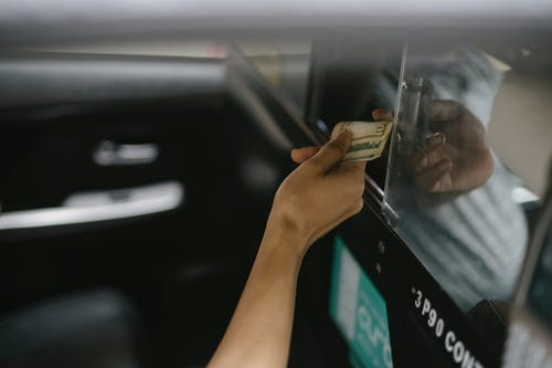 Interior of modern taxi car while passenger paying for ride