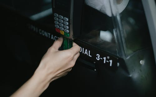 Crop anonymous traveler using card device while paying for taxi ride in automobile