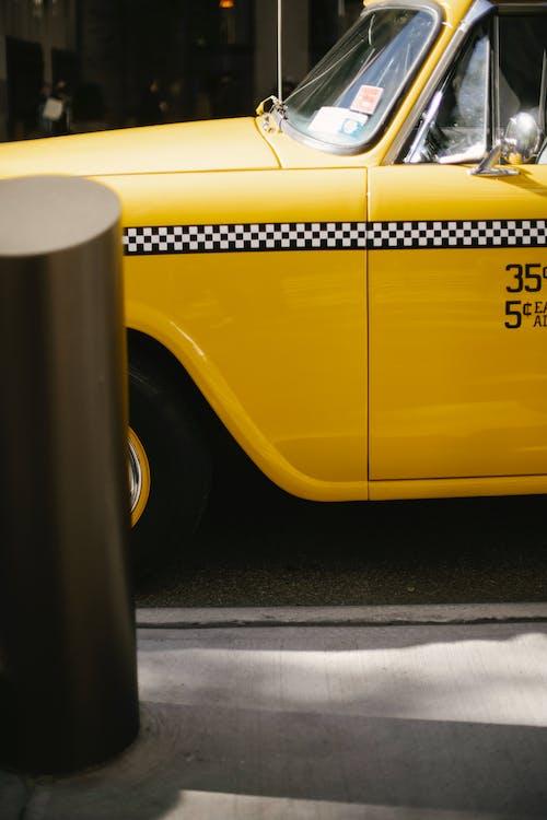 Yellow modern cab driving along roadway
