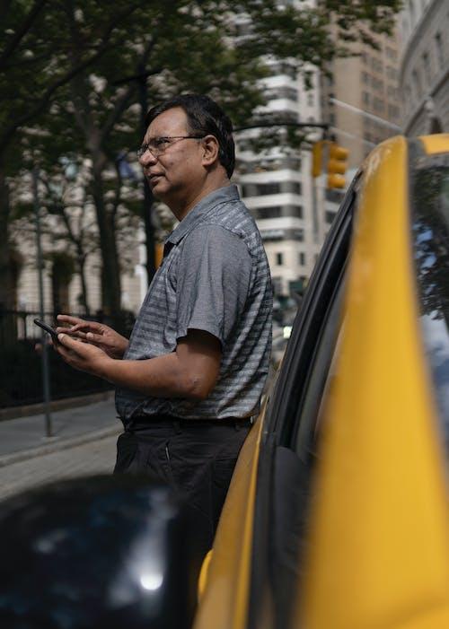 車の近くにスマートフォンを持つ民族の男