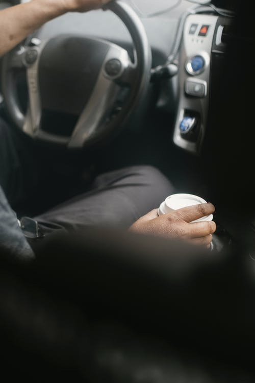 Unrecognizable driver with cup of coffee