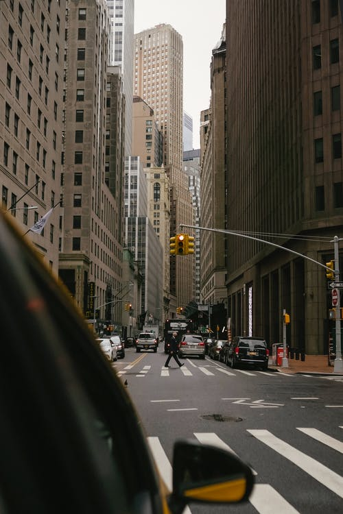 Taxi car on crossroad of asphalt road with zebra and vehicles in city downtown with high skyscrapers