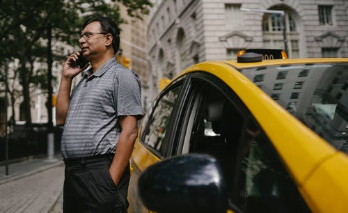 Serious ethnic male taxi driver with hand in pocket having conversation on cellphone while standing near car