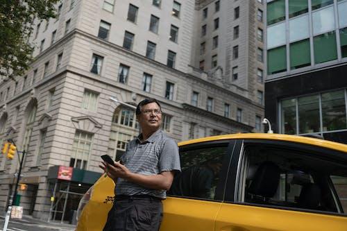 Homem Sério E étnico Parado Perto De Um Táxi Com Smartphone