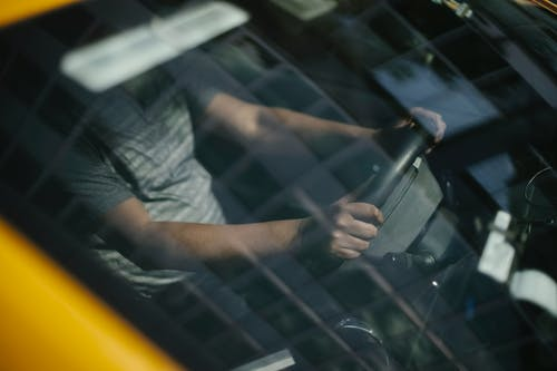 Through glass of windshield of ethnic crop male driver in cab while working in city
