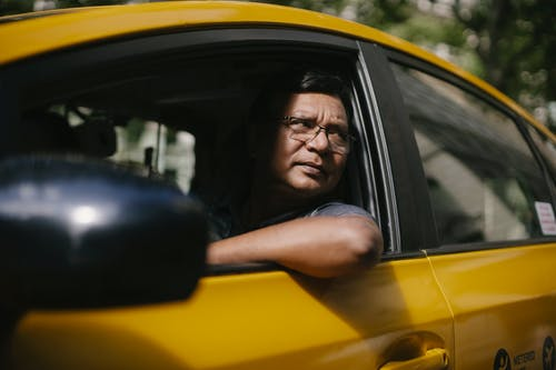 Serious ethnic male driver looking at opened window of taxi