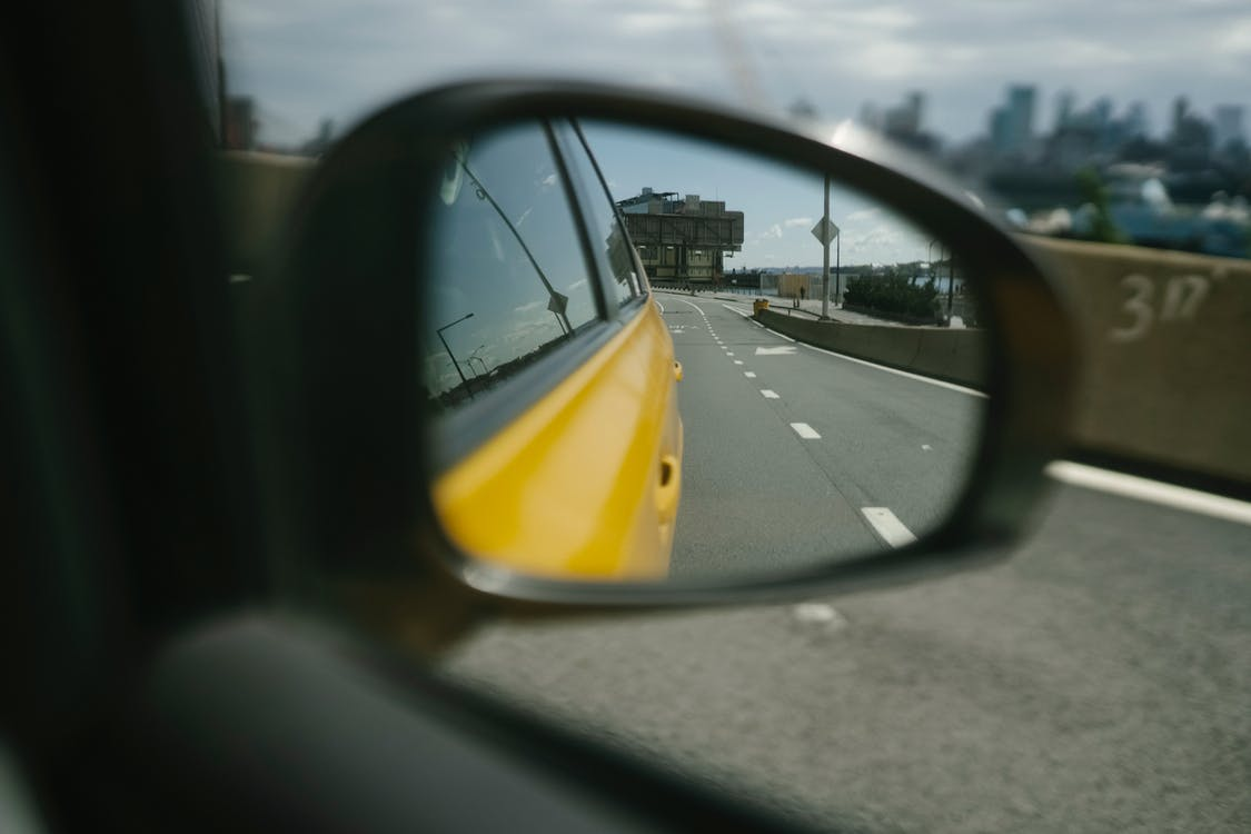 Side mirror of car reflecting road with marks and building on sunny day