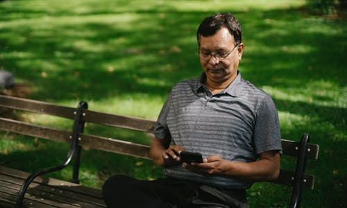 Ethnic male in casual outfit using smartphone while sitting on bench on park