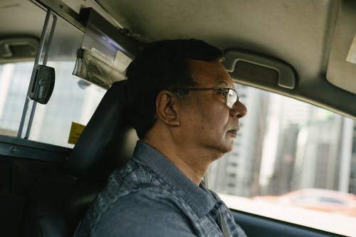 Side view of ethnic male in eyeglasses and casual clothes looking away while driving car