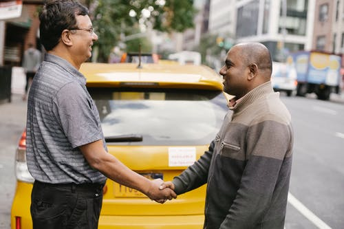 Side view of smiling ethnic men shaking hands and greeting each other while standing on street near taxi car