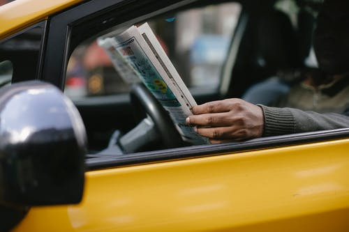Side view of crop anonymous ethnc male driver reading information in newspaper article while waiting for client