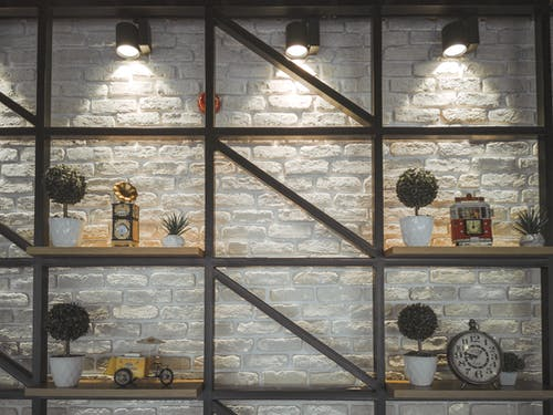 Different clocks with ornament and potted plants on wooden shelves near rough wall illuminated by shiny lamps in house
