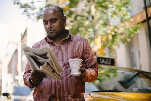 Interested adult ethnic male taxi driver with disposable glass of hot drink reading newspaper near vehicle on city street
