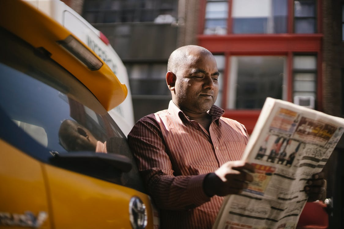 Interested ethnic cab driver reading newspaper on street