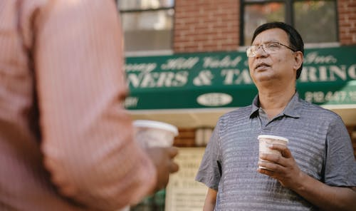 Attentive middle aged Asian male in eyeglasses with takeaway coffee talking to crop anonymous partner on city street