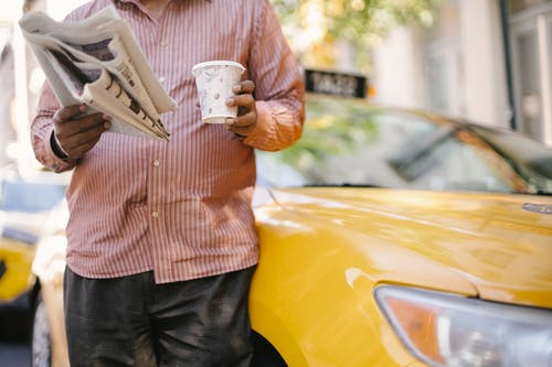 Faceless ethnic taxi driver with coffee to go and newspaper
