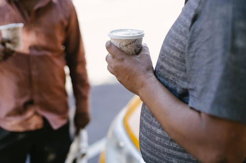 Crop unrecognizable ethnic male coworkers with takeaway coffee conversing near taxi car on urban roadway