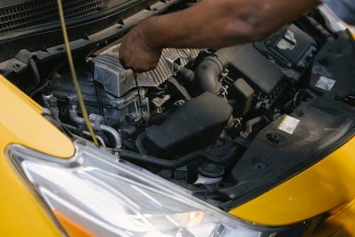 Crop ethnic mechanic revising modern taxi transport bonnet