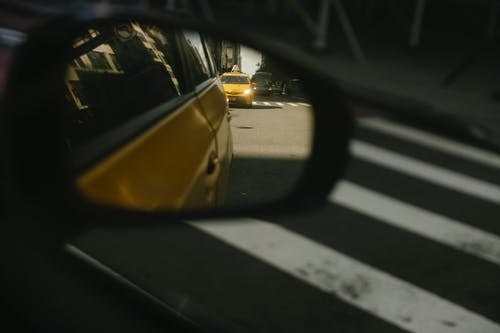 Modern taxi cars driving on road with crosswalk