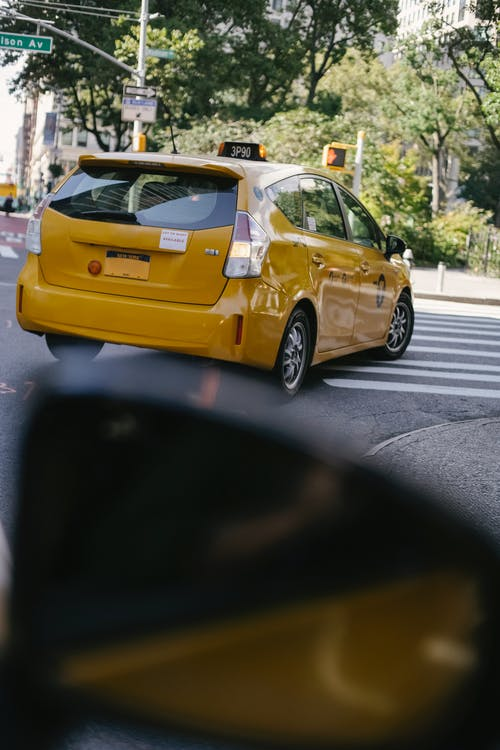 From inside vehicle view of modern colorful cab auto driving on asphalt roadway with crosswalk in town