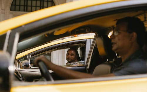 Multiethnic cab drivers speaking in automobiles in town