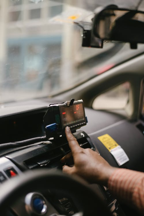 Crop ethnic man using GPS in cab