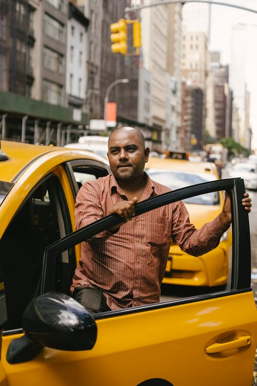 Ethnic man getting into yellow taxi