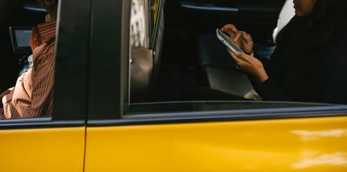 Side view of unrecognizable passenger browsing smartphone while sitting on backseat of yellow cab with anonymous driver during ride