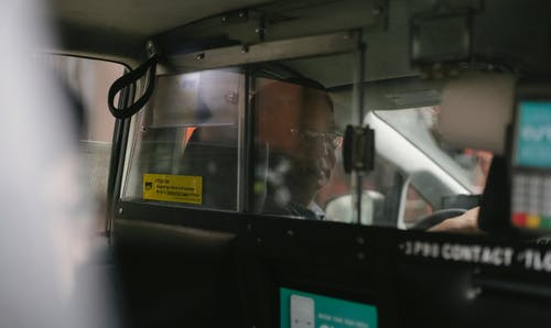 Ethnic driver in taxi with partition