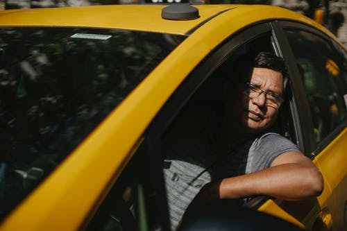 Adult male driver in glasses sitting in yellow cab and working while looking at camera
