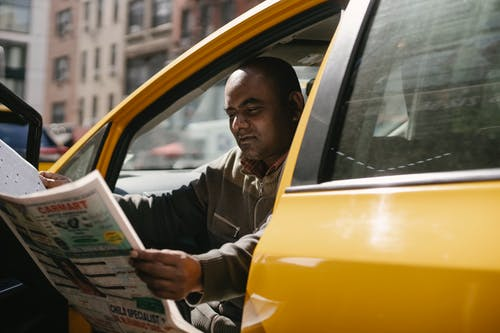 Concentrated male driver in casual clothes sitting in taxi during break and reading newspaper